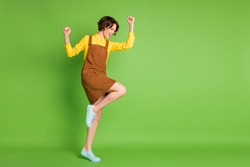 Full length profile photo of amazed positive girl raise fists wear yellow shirt overall footwear isolated green color background