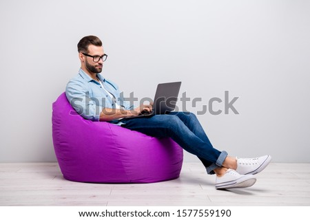 Full length profile photo of attractive guy holding notebook browsing chatting colleagues sitting comfy soft armchair wear specs casual denim outfit isolated grey color background
