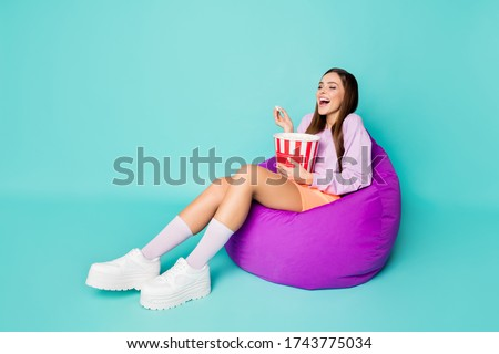 Full length profile photo of crazy lady sit bean bag chair eat popcorn watch comedy show laughing wear purple sweater orange mini skirt shoes socks isolated teal color background