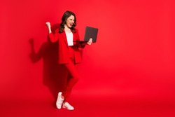Full length profile photo of cute young girl hold laptop raise fist up wear blazer trousers sneakers isolated red color background