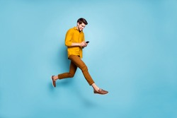 Full length profile photo of funny guy jumping high holding telephone millennial writing email walking down street wear yellow shirt pants isolated blue color background