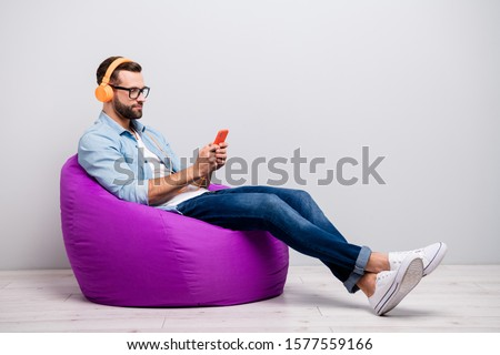 Full length profile photo of funny guy sitting comfy armchair holding telephone using cool earflaps choose song wear specs casual denim outfit isolated grey color background