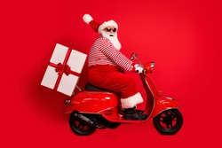 Full length profile photo of grandfather grey beard ride retro scooter deliver gift wear santa claus x-mas costume suspenders sunglass striped shirt boots cap isolated red color background