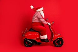 Full length profile photo of grandfather grey beard ride vintage motorbike wear santa claus x-mas costume suspenders sunglass striped shirt cap gloves isolated red color background