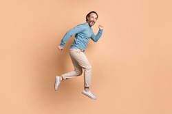 Full length profile photo of guy jump rush wear glasses blue sweater pants footwear isolated beige color background