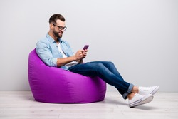 Full length profile photo of positive guy sitting comfy violet armchair holding telephone chatting friends wear specs casual denim outfit isolated grey color background