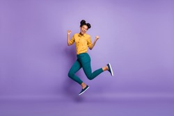 Full length profile photo of pretty dark skin lady jumping high celebrating favorite team victory wear casual yellow shirt trousers isolated purple color background