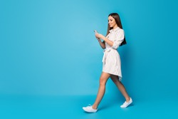 Full length profile photo of pretty lady freelancer hold telephone arms read positive blog comments walk street wear casual spring striped mini dress isolated blue color background
