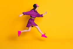 Full length profile portrait of attractive lady running headwear magenta outfit isolated on yellow color background