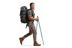Full length profile shot of a bearded guy hiker with a backpack and hiking poles walking isolated on white background
