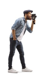 Full length profile shot of a bearded guy recording with 8mm vintage camera isolated on white background