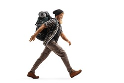 Full length profile shot of a bearded hiker with a backpack walking fast isolated on white background