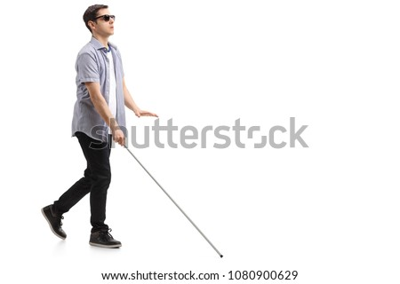 Full length profile shot of a blind young man with a cane walking isolated on white background