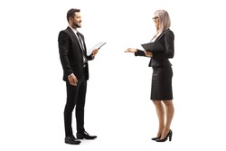 Full length profile shot of a businessman and businesswoman having a conversation isolated on white background