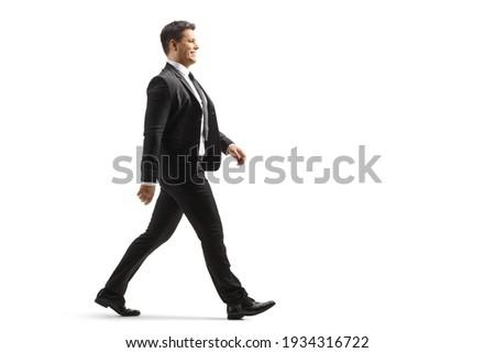 Full length profile shot of a businessman walking isolated on white background
