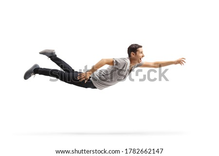 Full length profile shot of a casual young man flying and reaching for something isolated on white background Photo stock ©