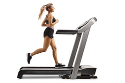 Full length profile shot of a female running on a treadmill isolated on white background