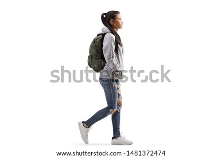 Full length profile shot of a female student wearing a hoodie and ripped jeans walking isolated on white background