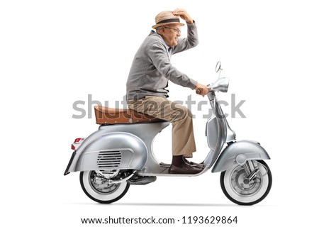 Full length profile shot of a gentleman riding a vintage motorbike isolated on white background #1193629864