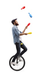 Full length profile shot of a male juggler on a unicycle juggling with clubs isolated on white background