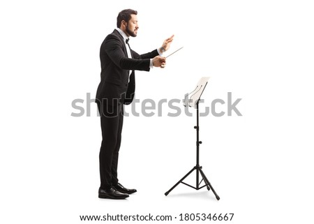 Full length profile shot of a male musical conductor directing with a notebook on a stand isolated on white background Foto stock ©