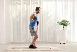 Full length profile shot of a man exercising with a resistance band at home isolated on white background