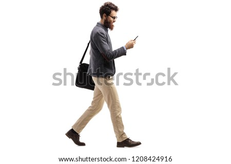 Full length profile shot of a man walking and looking into a mobile phone isolated on white background