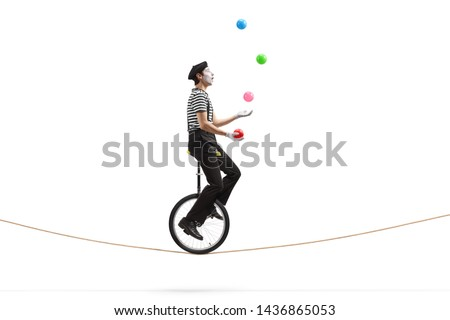 Full length profile shot of a mime riding a unicycle on a rope and juggling with balls isolated on white background #1436865053