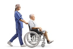Full length profile shot of a nurse pushing a hospitalized mature patient in a wheelchair isolated on white background
