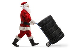 Full length profile shot of a santa claus pushing car tires on a hand truck isolated on white background