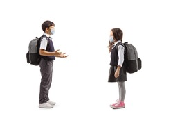 Full length profile shot of a schoolboy and a schoolgirl wearing face masks and talking isolated on white background