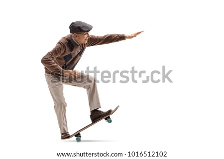 Full length profile shot of a senior riding a skateboard and doing a manual isolated on white background