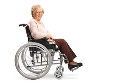 Full length profile shot of a senior woman in a wheelchair smiling at the camera isolated on white background