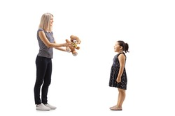 Full length profile shot of a woman giving a teddy bear to a girl  isolated on white background