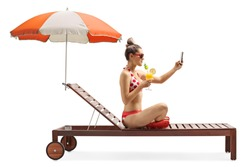 Full length profile shot of a woman in bikini taking a selfie photo and drinking coctail on a sunbed under umbrella isolated on white background