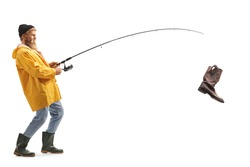 Full length profile shot of a young bearded fisherman with an old boot on a fishing rod isolated on white background