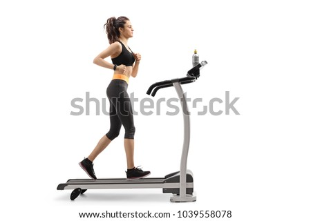 Full length profile shot of a young fitness woman running on a treadmill isolated on white background