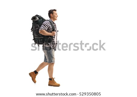 Full length profile shot of a young hiker walking isolated on white background #529350805