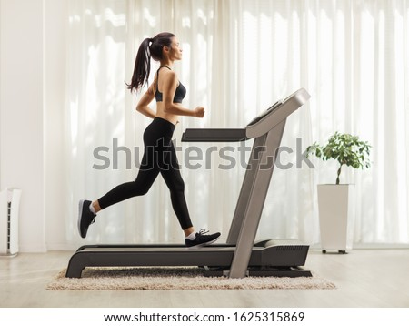 Full length profile shot of a young woman running on a treadmill indoors