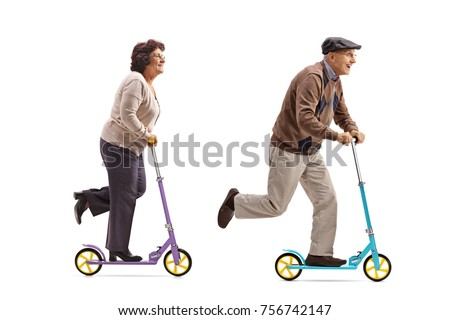 Full length profile shot of an elderly woman and an elderly man riding scooters isolated on white background