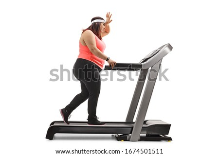 Full length profile shot of an overweight woman exercising on a treadmill and holding her forhead isolated on white background Сток-фото ©
