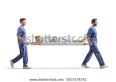 Full length profile shot of healthcare workers carrying a female patient on a stretcher isolated on white background Сток-фото ©