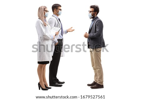 Full length profile shot of male and female doctors wearing protective medical masks and talking to a man with a medical face mask isolated on white background