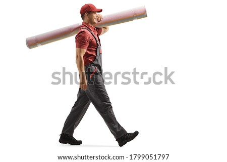 Full length profile shot of male worker carrying a carpet and walking isolated on white background ストックフォト ©
