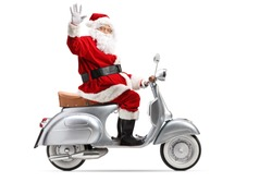 Full length profile shot of Santa Claus riding a vintage motorbike and waving isolated on white background