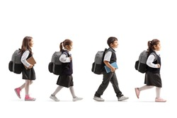 Full length profile shot of schoolchildren in uniforms walking in line isolated on white background