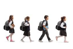 Full length profile shot of schoolchildren in uniforms walking in line isolated on white background