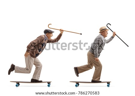 Full length profile shot of two elderly men with canes riding longboards isolated on white background #786270583