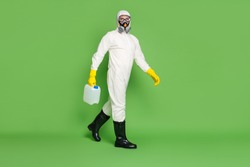 Full length profile side photo medical worker man hold canister liquid cleaner disinfect stop ncov epidemic spread wear white hazmat uniform boots isolated green color background