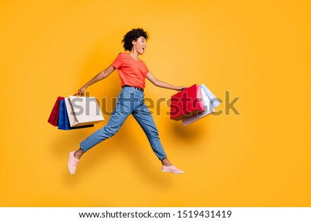 Full length profile side photo of amazed  funky funny wavy  brunette hair girl hold bags jump run to shopping center boutique hurry wear red t-shirt denim jeans  isolated over yellow color background